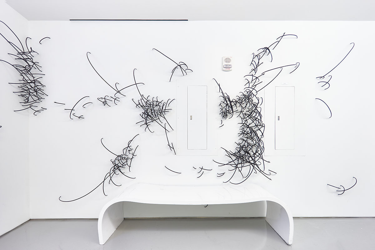 Sculpture of white bench in front of white wall with cable-like projections coming out