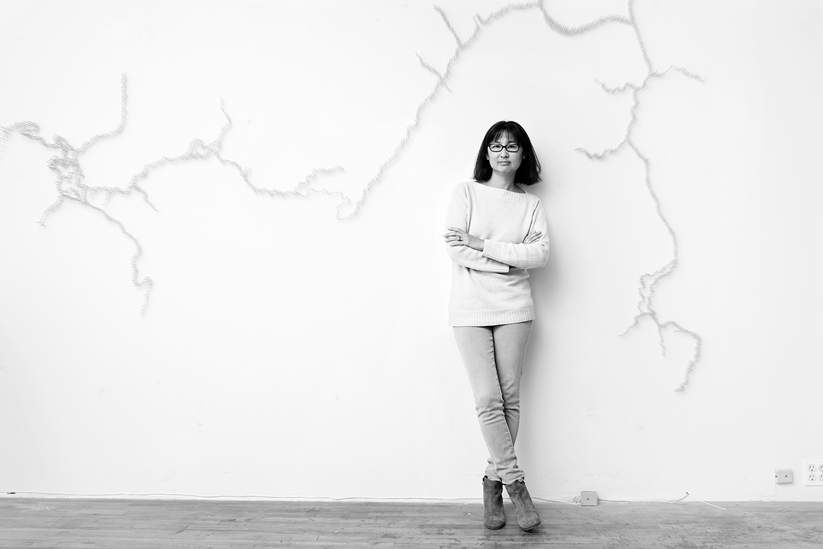 Black and white portrait of Maya Lin against a dead tree