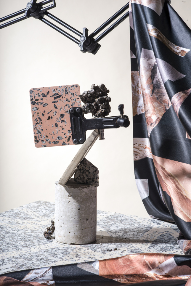 A piece of pink terrazzo suspended by a clamp on a concrete plinth, Granito.