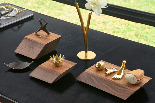 A selection of gold and brass keepsakes on top of walnut pedestals