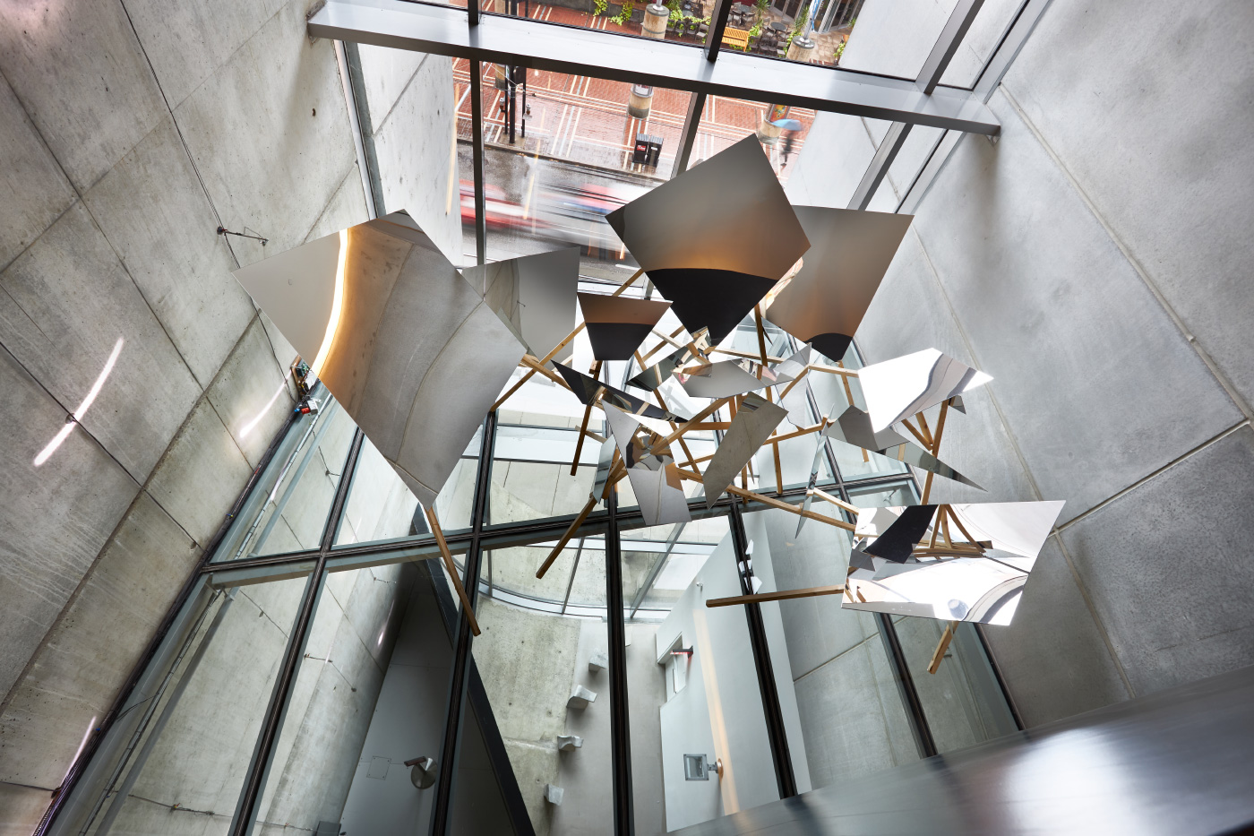 Interior photo of a metal sculpture suspended in a concrete atrium