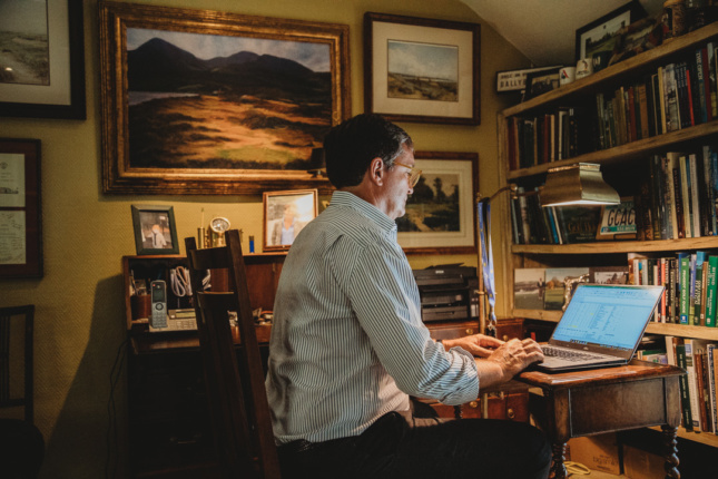 Image of man typing at computer in his study