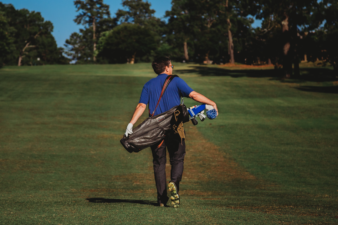 Image of man walking on golf course carrying his bag