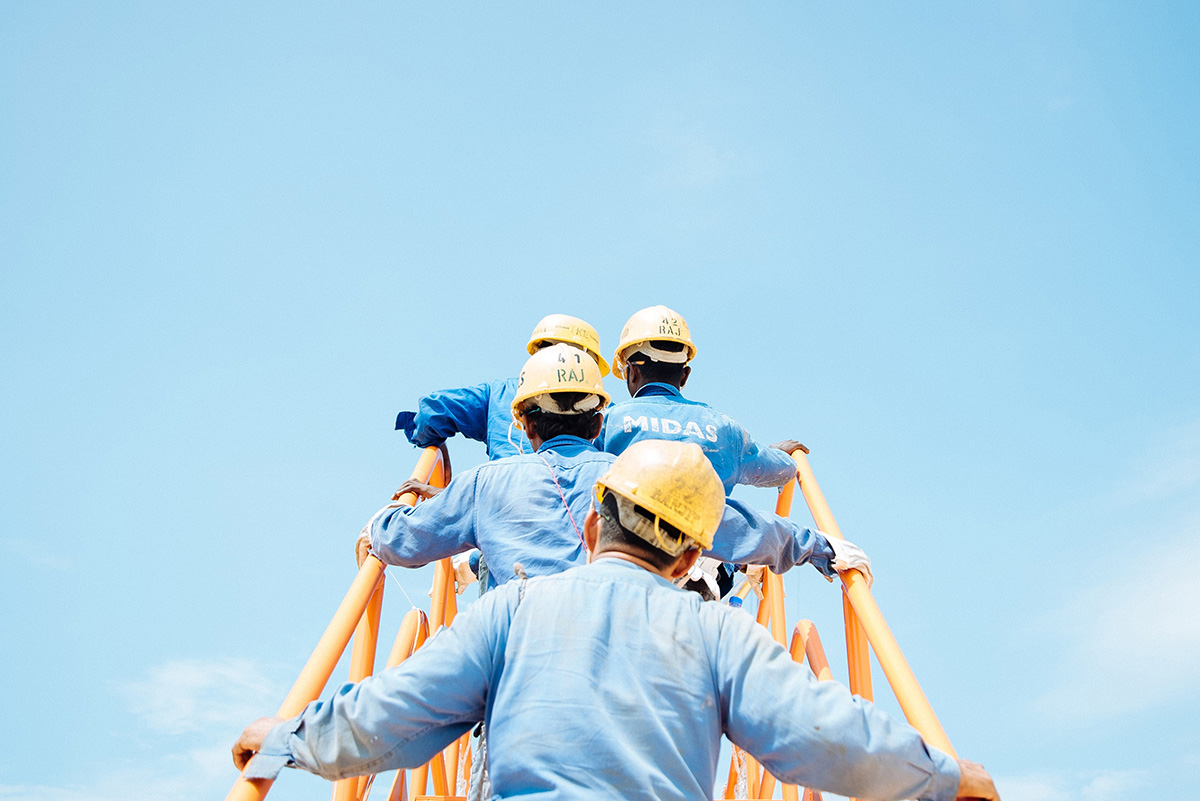 Image of workers climbing ladder together