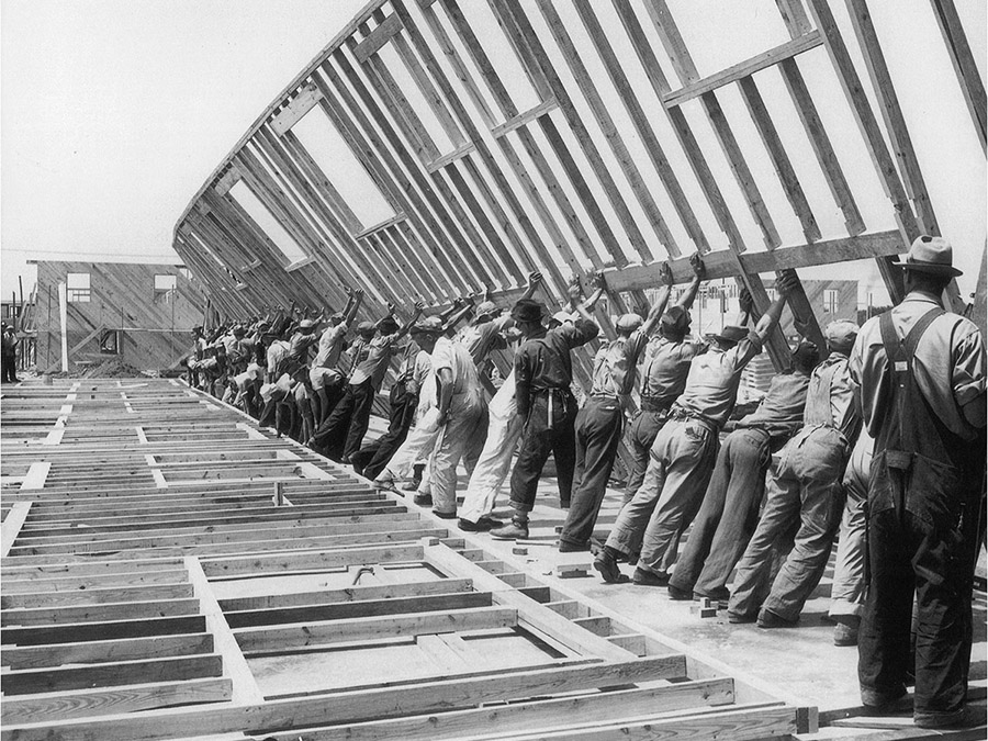 Black and white image of men lifting wood frame wall for house, part of the Venice Architecture Biennale