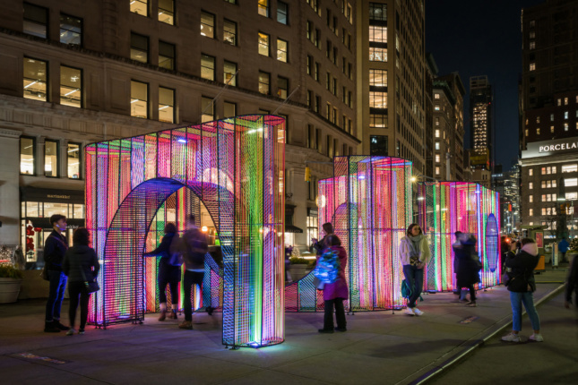 Photo of people moving below lit-up neon arches