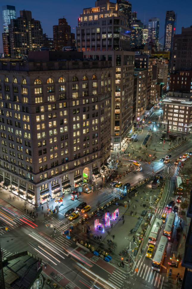 Aerial photo of the plaza in front of the Flatiron Building with lit-up pavilion
