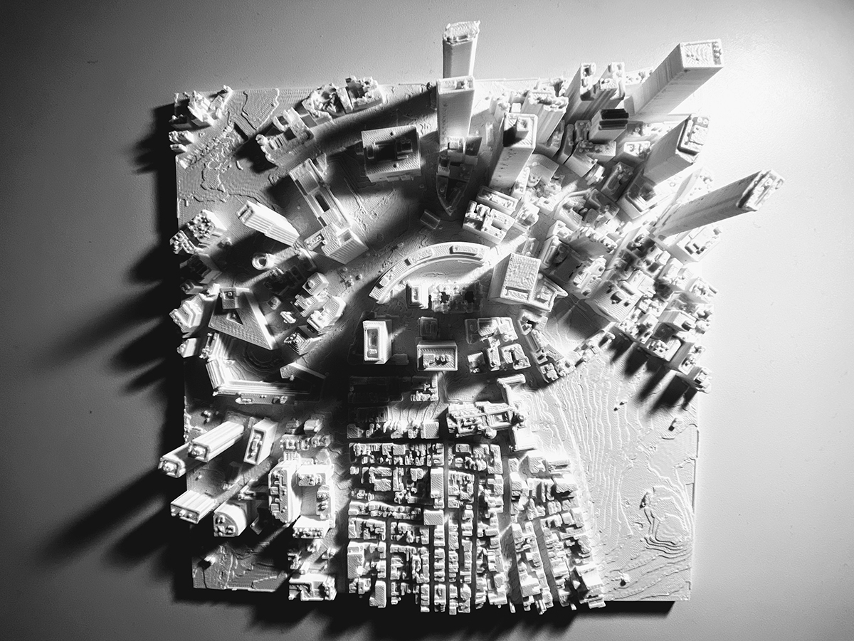 A top-down view of a white plastic tile with a 3D map of a city.