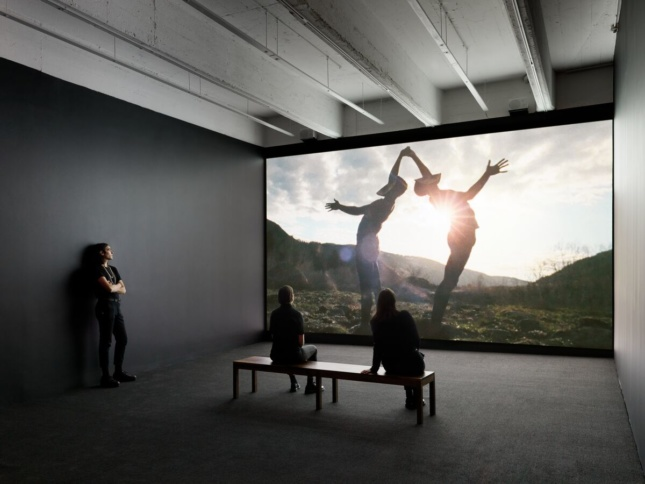 Installation view of a film with two masked dancers