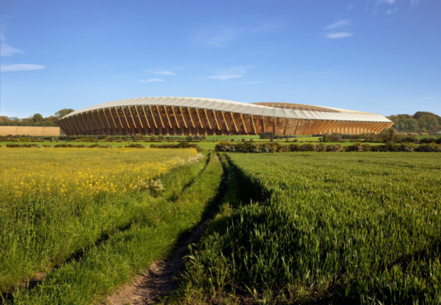 A timber-constructed football stadium sits in a field with blue skies