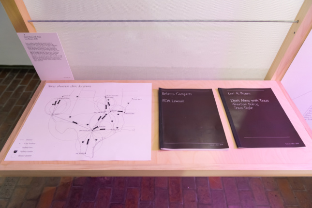 A table with a map of texas and takeaway books on abortion access