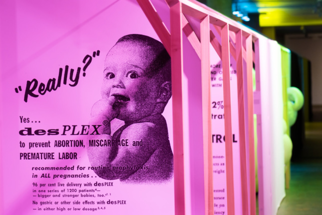 A pink wall text with a baby
