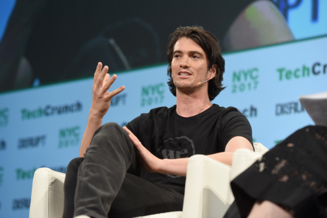 A man sitting on stage during a WeWork presentation