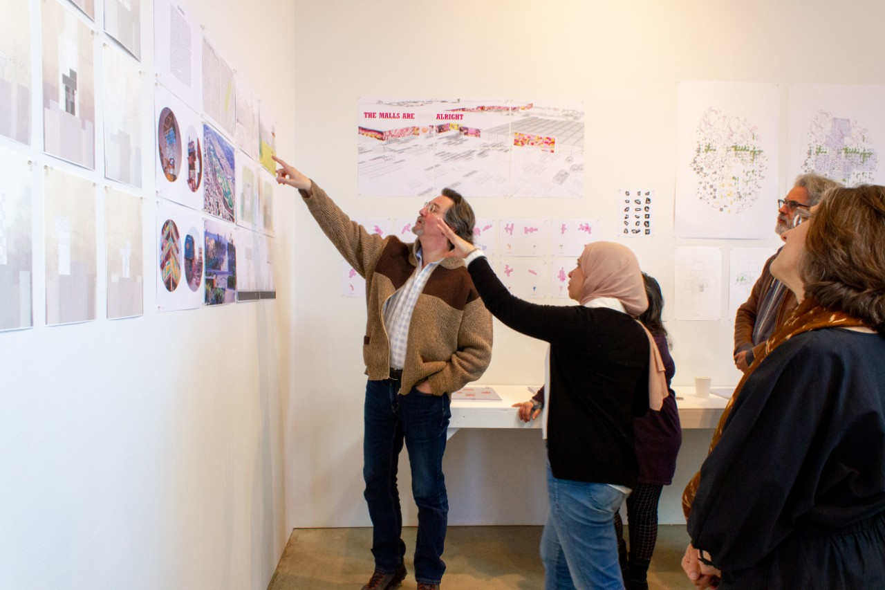 A group of people look at drawings pinned up on a wall for an architecture review
