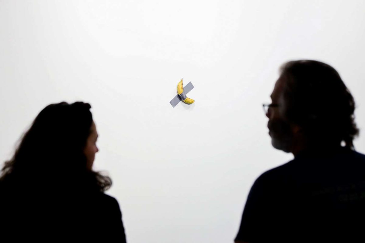 A banana taped to a wall at Art Basel Miami 2019, with onlookers