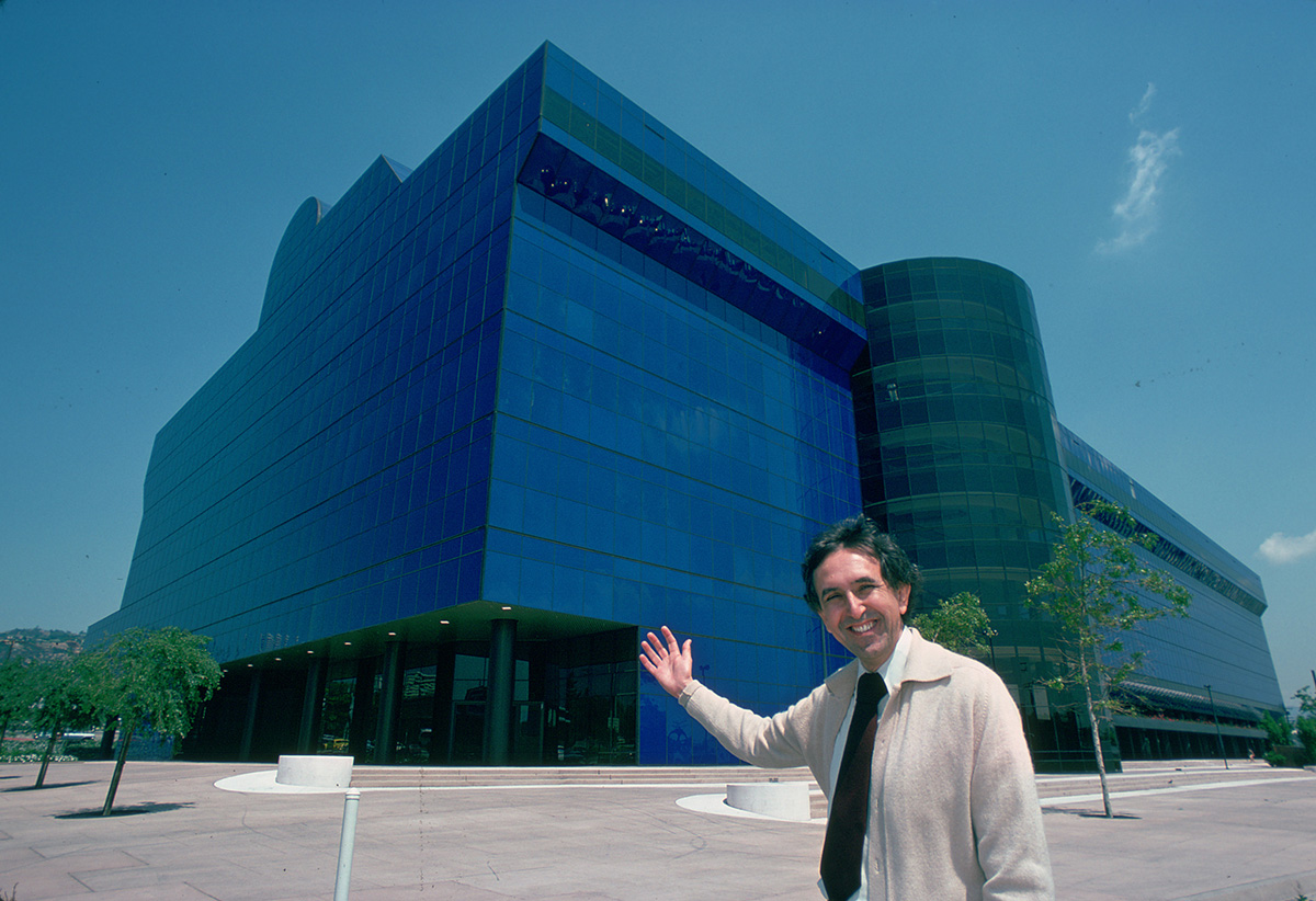 Image of man in front of blue glass building