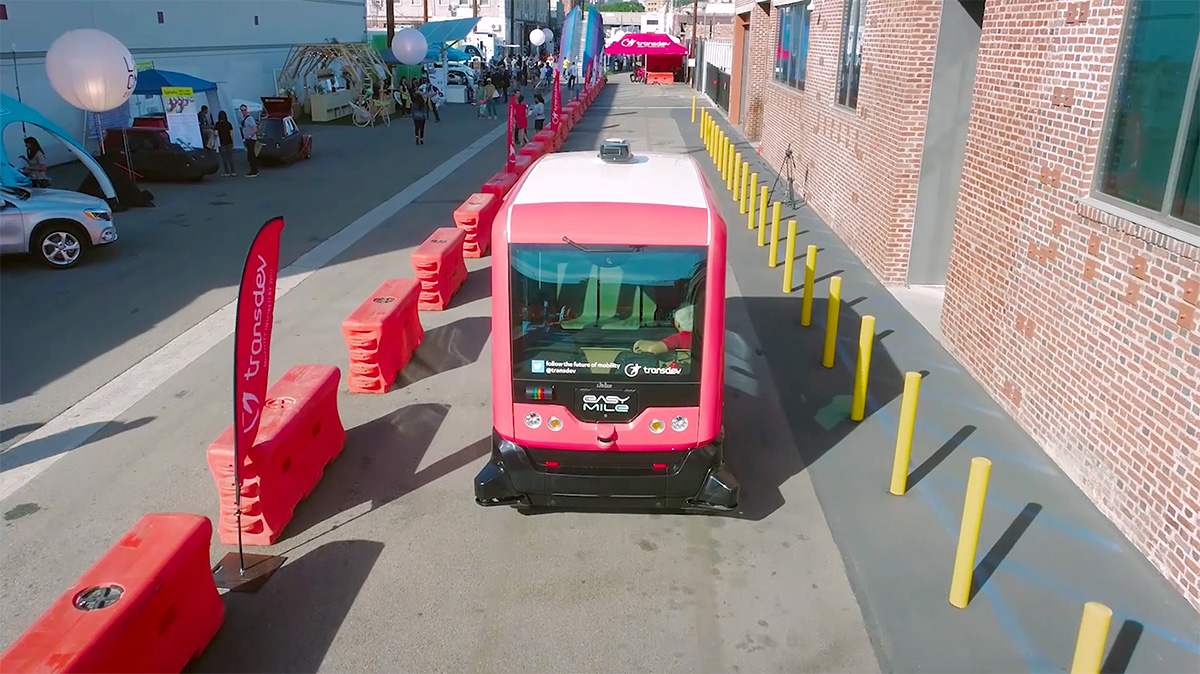A red-and-white autonomous shuttle at CoMotion