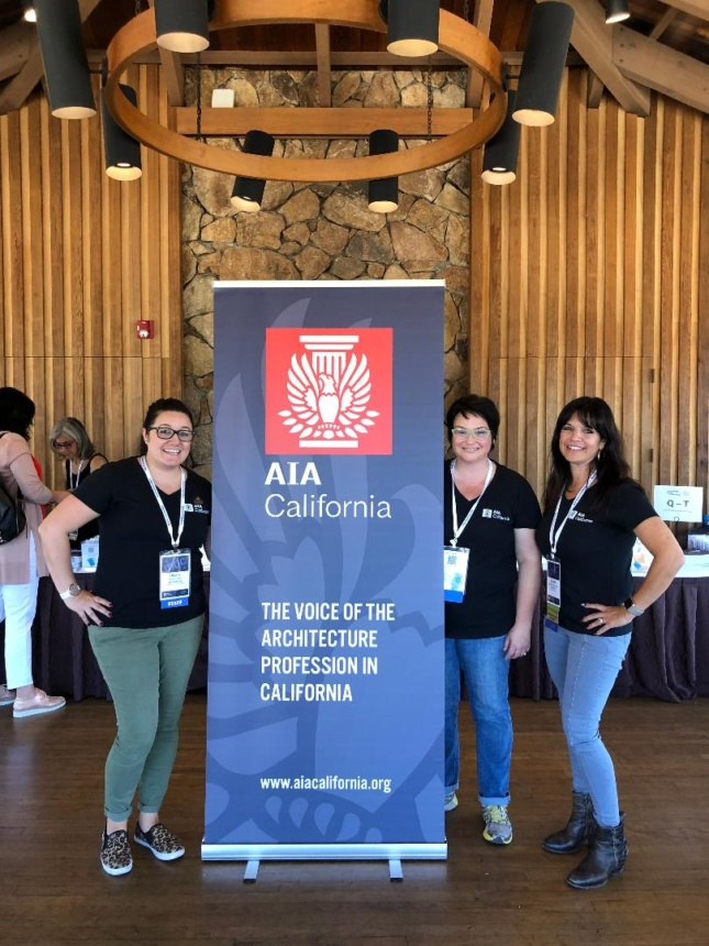 Conference goers by a banner that reads AIA California