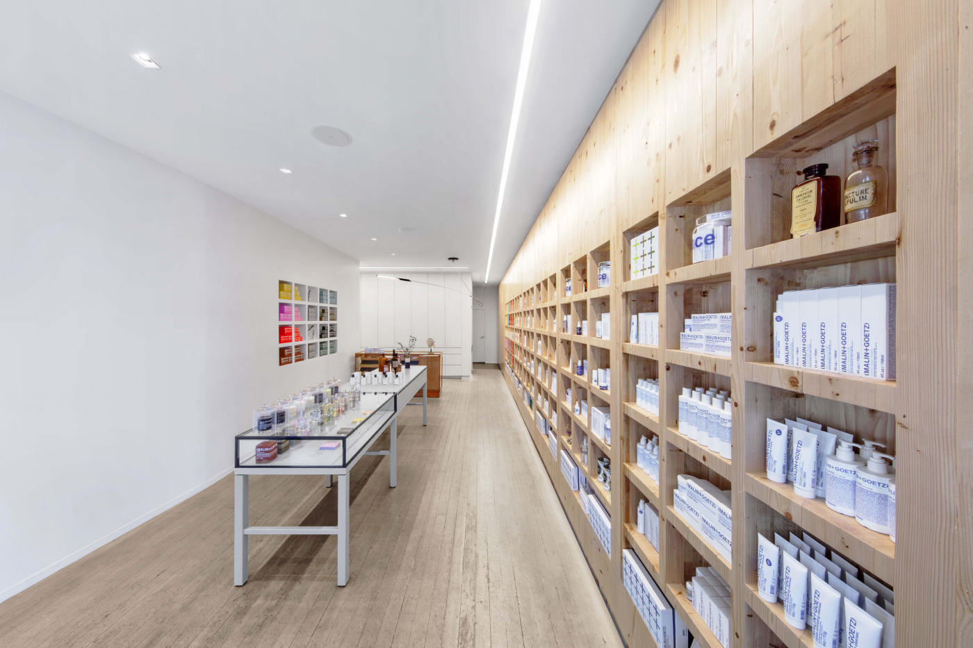 Interior photo of a linear retail store with timber shelving in a Malin + Goetz store