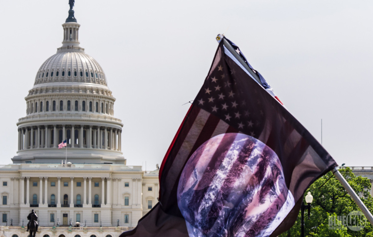 Image of US Capitol dome with flag in front of it depicting the world