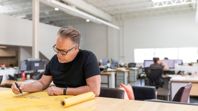 An architect sits at a work table with a roll of trace