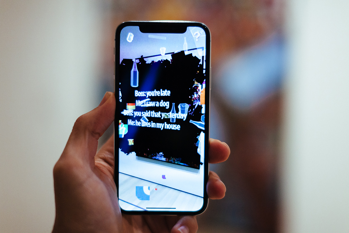 An iPhone that shows floating bottles and other digital artifacts with white text on black scribbles that reads