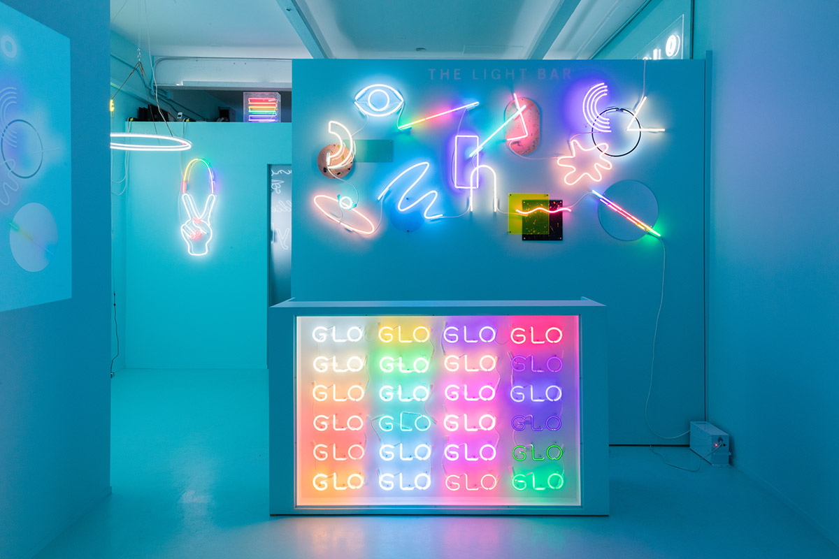 Neon signs that read Name Glo in a teal storefront