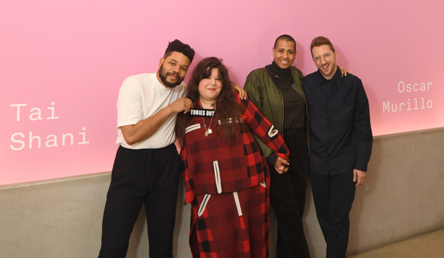 A group portrait of four people against a pink background at the turner prize awards