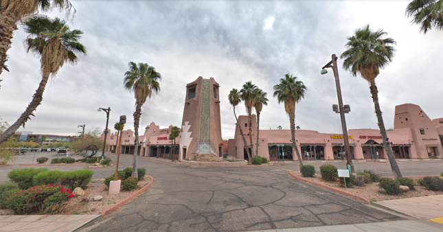 A photo of a strip mall rendered in pink adobe, with a sign that says Papago Plaza