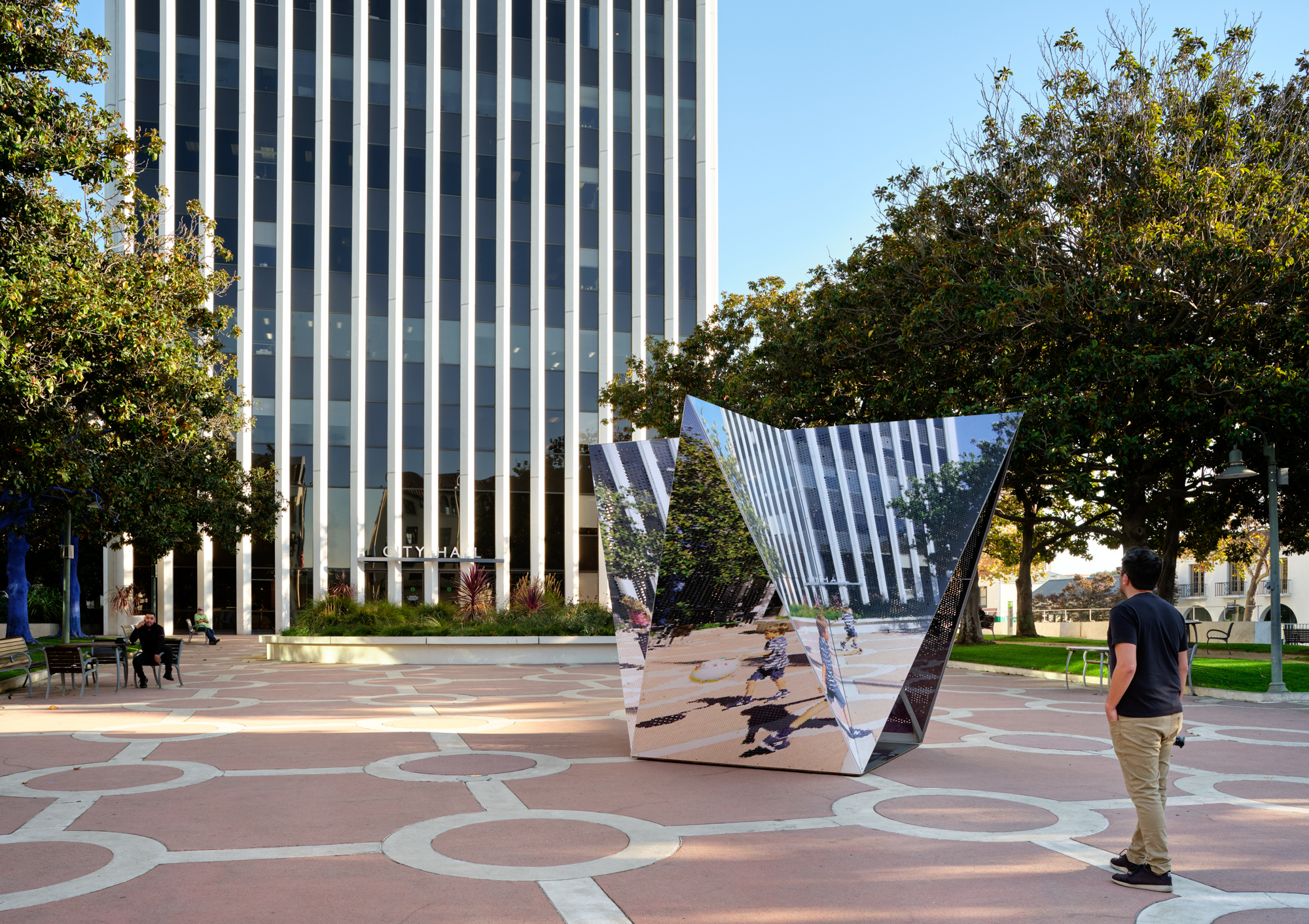A man walking by a mirrored crystal structure in Palo Alto
