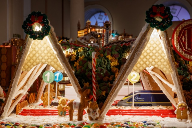 a gingerbread train station with a miniature working train passing through