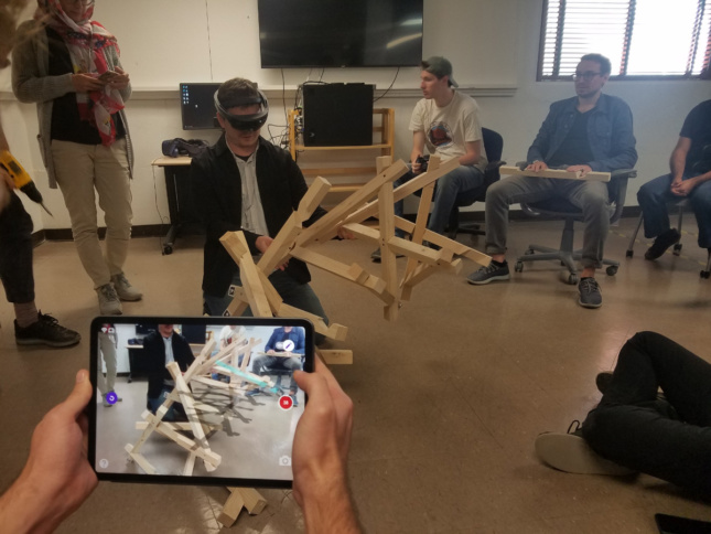 People in VR headsets interacting with wood structures