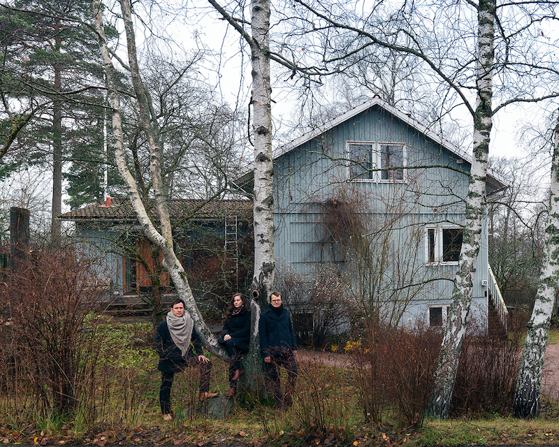 Image of three architecture curators in front of timber-clad house in the woods