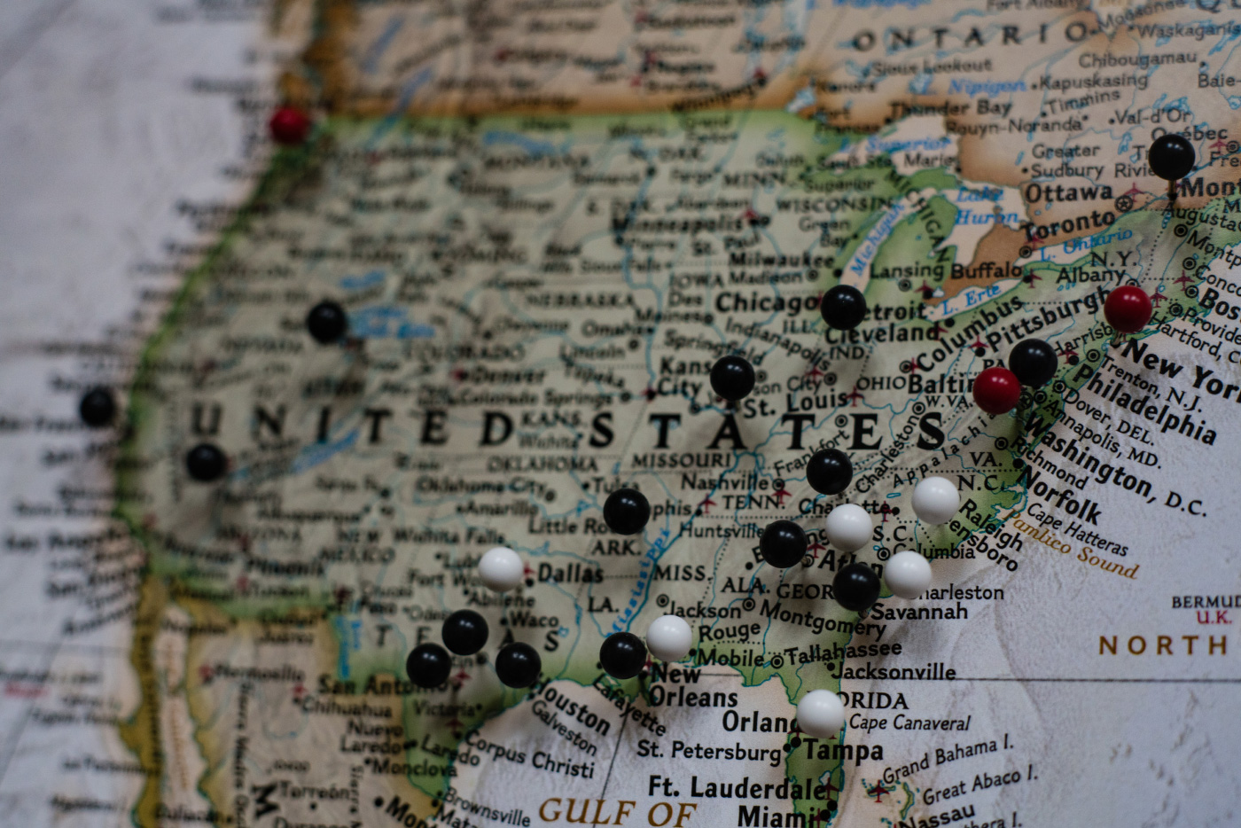 A map of the United States with black and white pins stuck into it