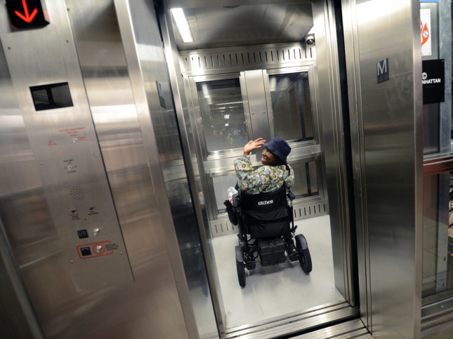 Image of woman in wheelchair waving inside subway station elevator