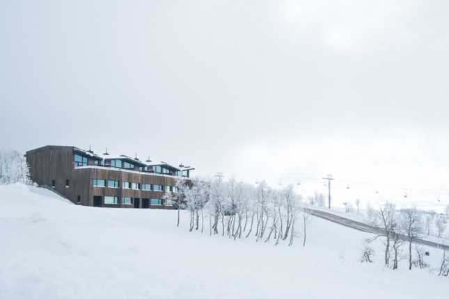 Exterior of a building atop a snowy hill.