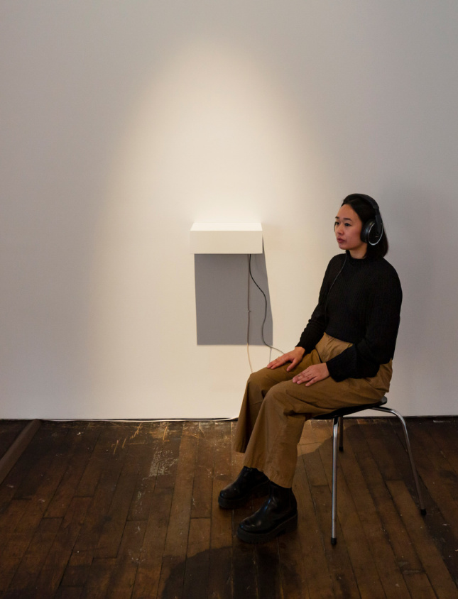 A woman listening to an audiobook in Peter Freeman gallery space
