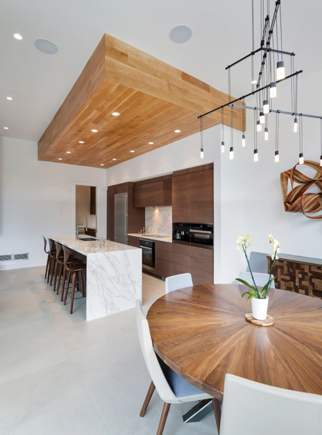 Interior shot of a kitchen island, dining room table, and chandelier