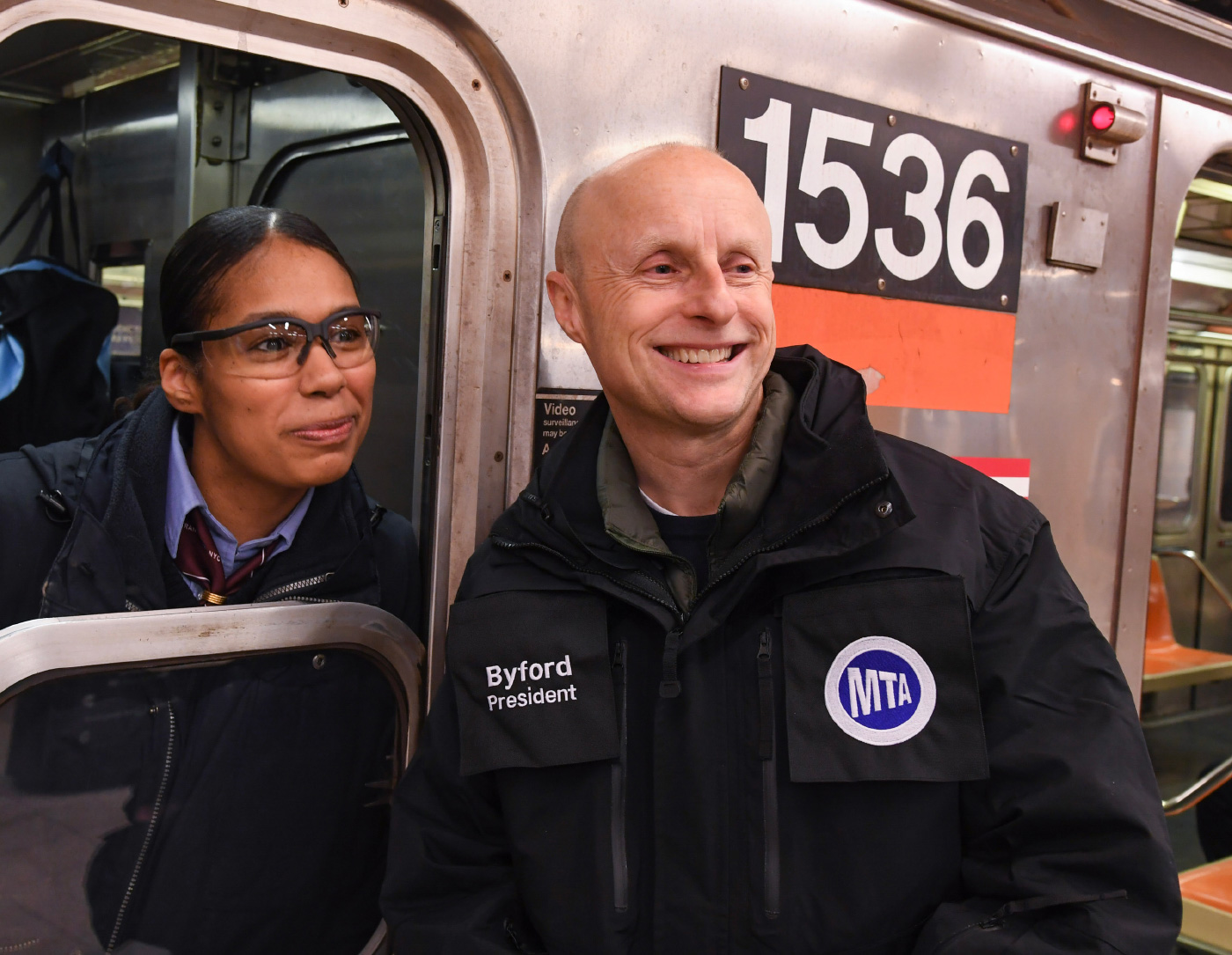 A smiling bald man, Andy Byford, in front of a train