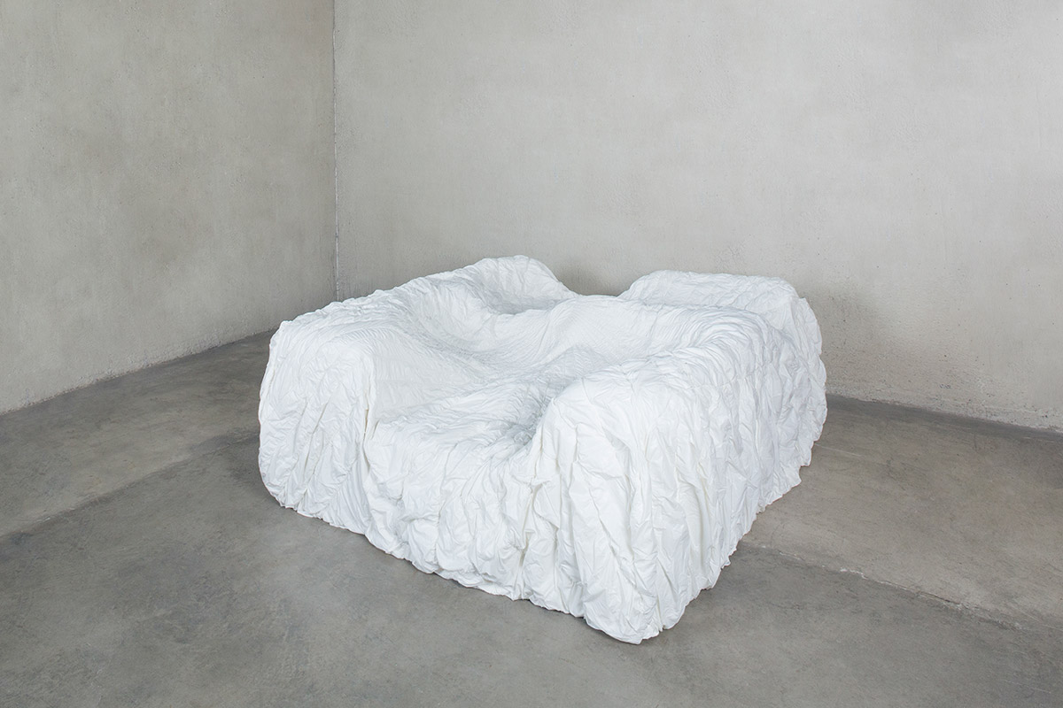 A white couch made from foam on a concrete floor