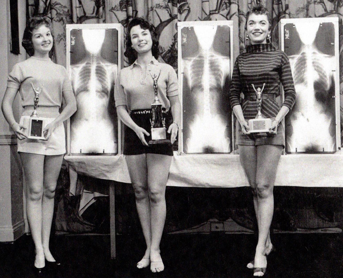 Black-and-white photo of three women with trophies, from X-ray architecture