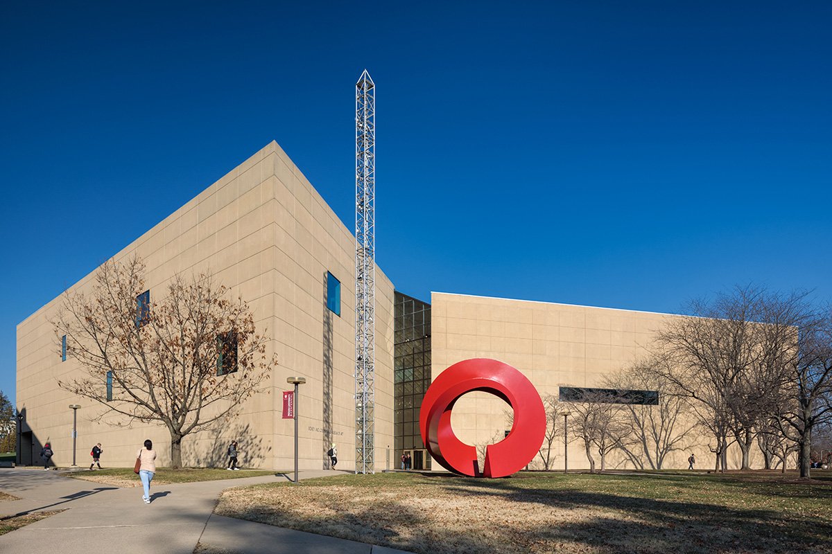 Exterior image of a limestone-clad museum and red circular sculpture in its front lawn