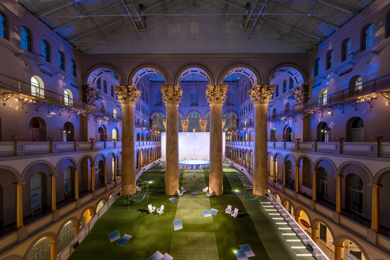 Inside of the National Building Museum, a lawn weaves between great pillars