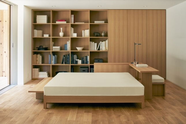 Inside a timber house, with a bed and Muji products on the walls