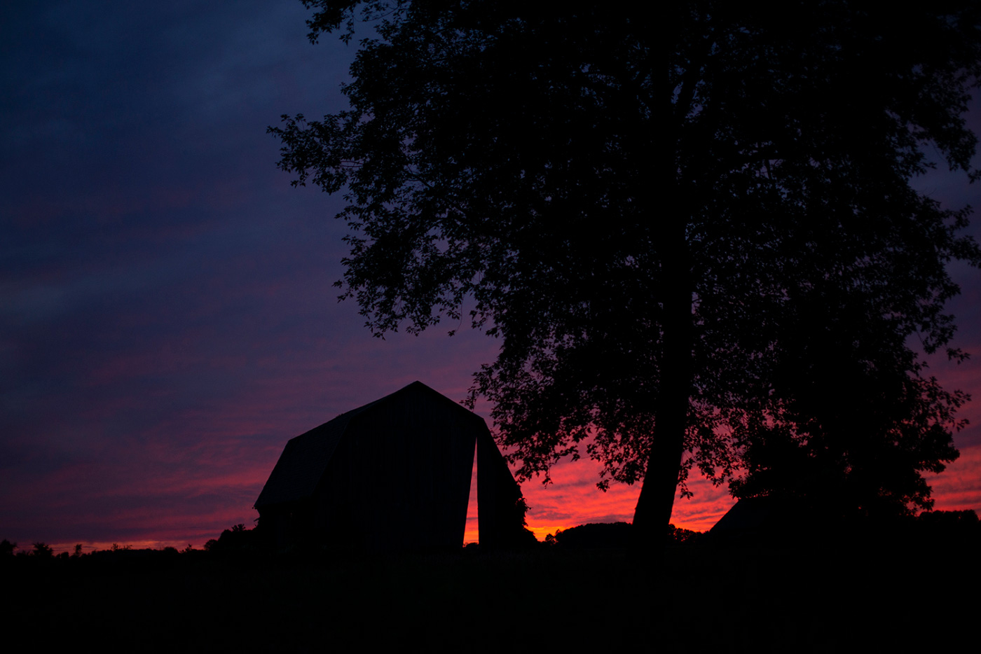 Silhouette of Secret Sky, a barn with a sliver cut out of it