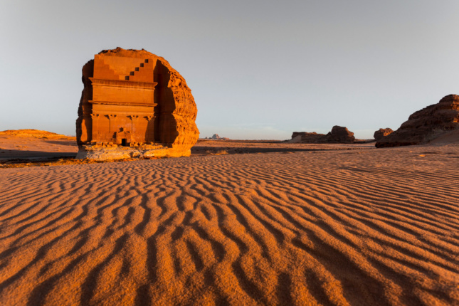A large facade carved out of a giant boulder in the desert.