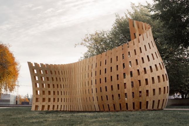 Photo of an upwardly cascading wall assembled from timber slats