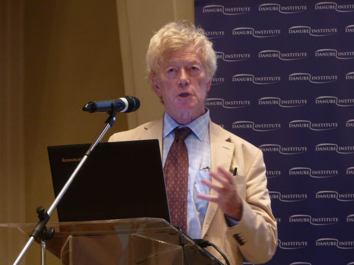 Roger Scruton, an older man with floppy hair, at a lectern