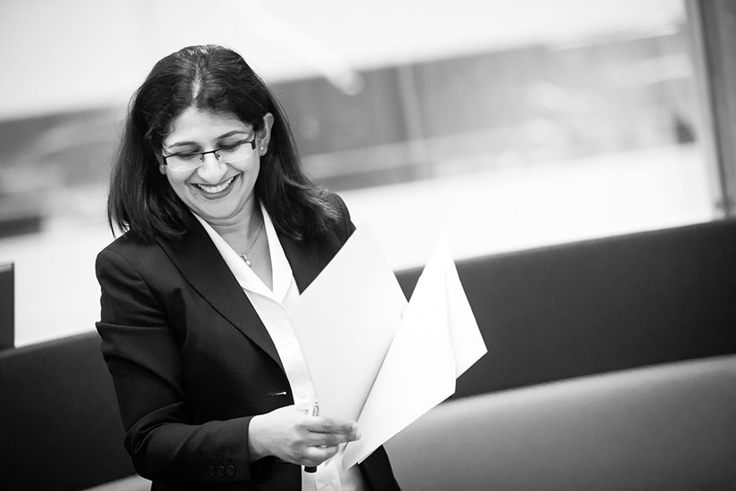 A black-and-white photo of a woman, Upali Nanda, in a dark suit smiling and holding papers.