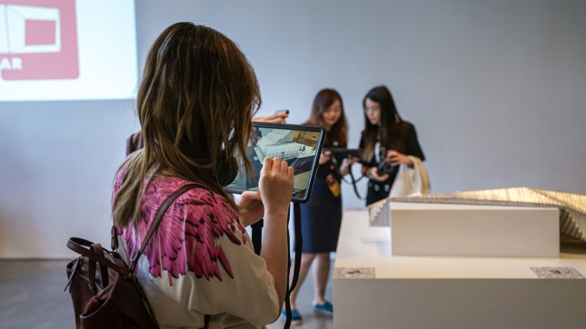 People using iPads in a museum space.